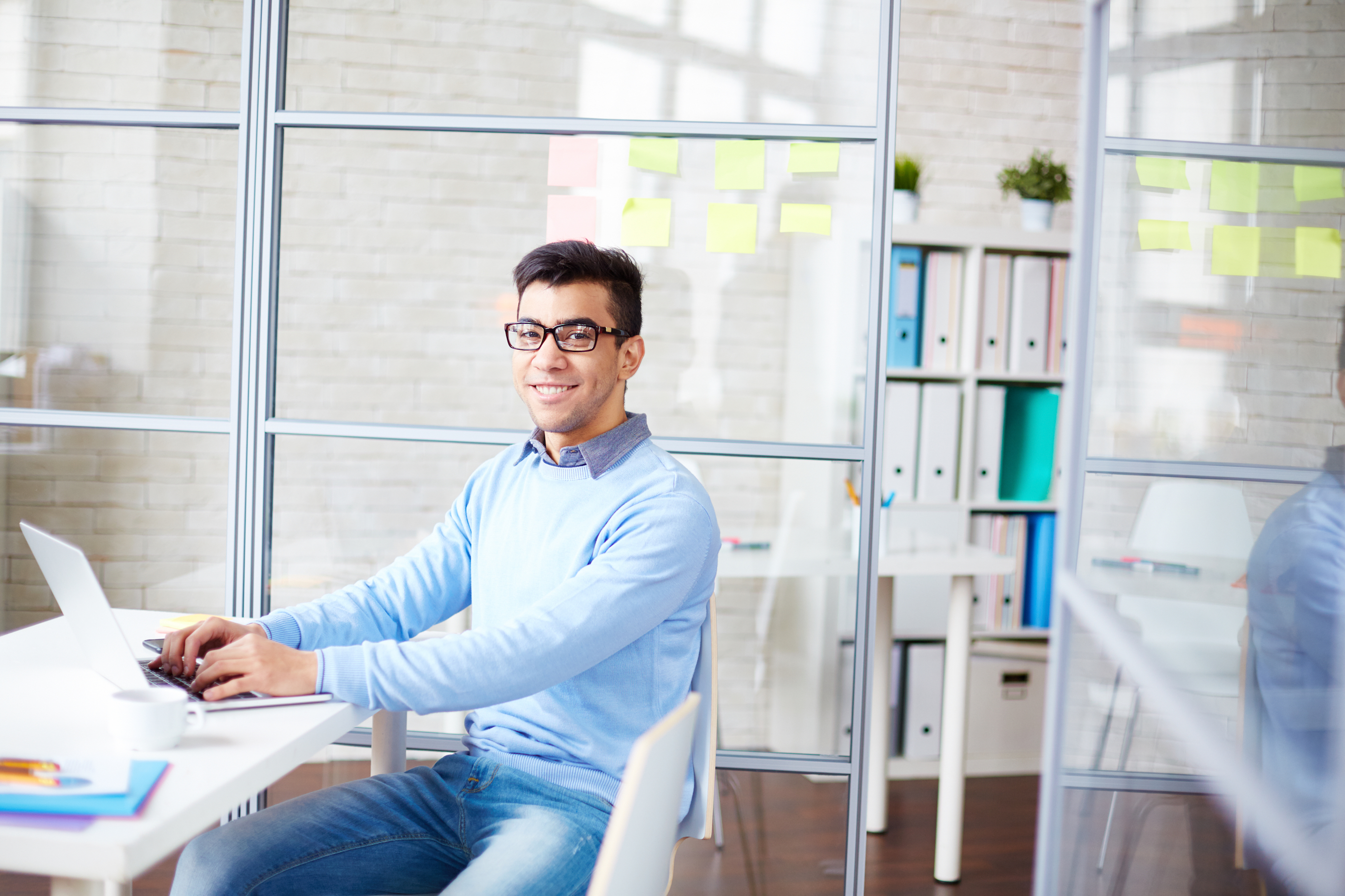 stock image of person at computer, smiling